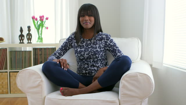 happy african american woman sitting cross legged on couch - cross legged stock videos & royalty-free footage