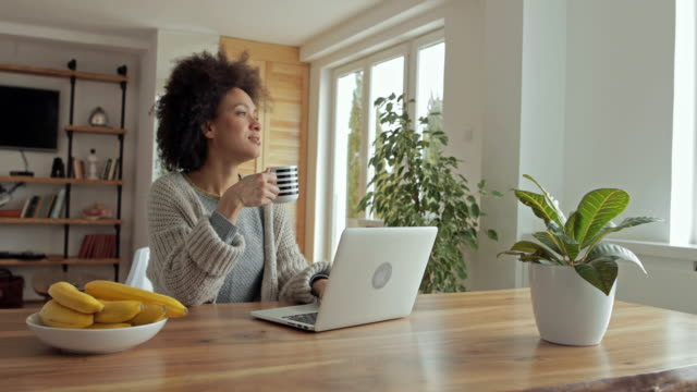 happy african american woman writing an e-mail on laptop and drinking coffee. - mug stock videos & royalty-free footage