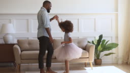 Happy african dad dancing with his child daughter princess