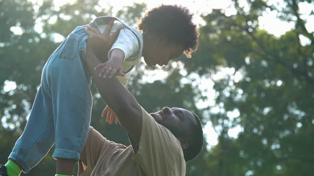 happy african family of father with son age 3 yearold having fun in the nature while son raises arms into air while open arms enjoying travel holidays.dad and baby boy playing together outdoors on a summer vacations with child.open arms concept. - wonderlust stock videos & royalty-free footage