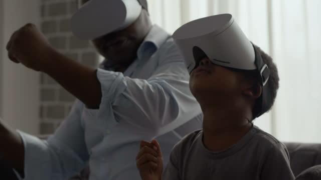 vidéos et rushes de bonne famille africaine de père avec son fils de 3 ans portant casque de réalité virtuelle et en regardant quelque chose futuriste autour de l'exposition de technologie interactive tout en rester à la maison pour prévenir les épidémies de coronavi - famille avec un enfant