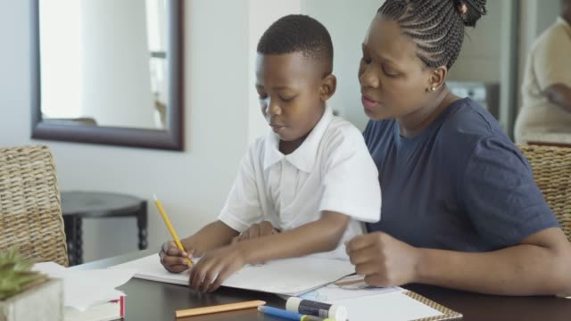 happy african woman helping her son doing homework - single parent family stock videos & royalty-free footage
