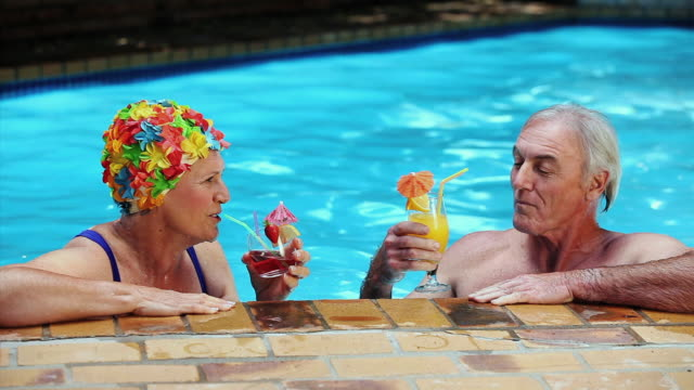 MS Happy aged couple toasting with cocktails in pool / Cape Town, Western Cape, South Africa