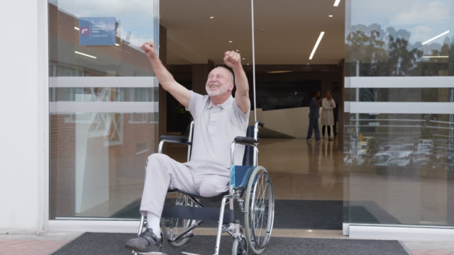 happy amputee patient on remission leaving the hospital in a wheelchair and celebrating with arms up - leaving hospital stock videos & royalty-free footage