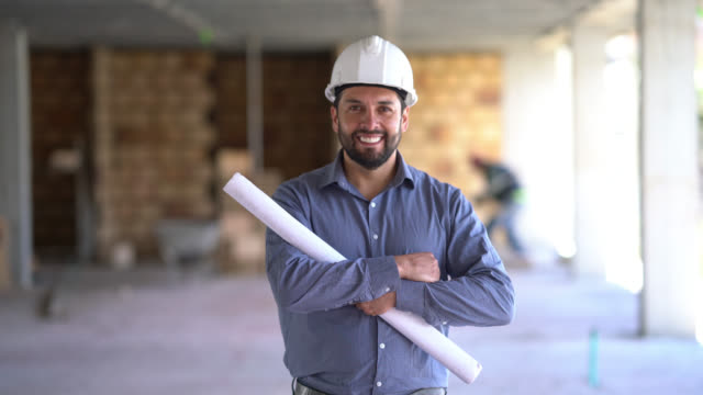 happy and confident architect walking towards the camera smiling with arms crossed - architetto video stock e b–roll