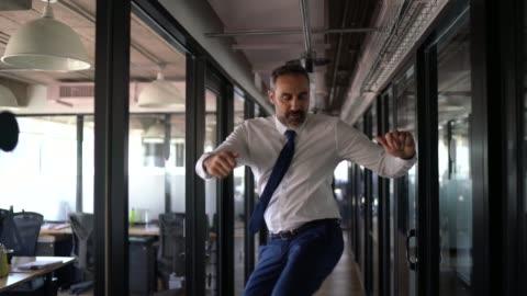 glad och trygg affärsman dansar på kontoret - framgång bildbanksvideor och videomaterial från bakom kulisserna