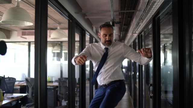 happy and confident businessman dancing in the office - estatico video stock e b–roll