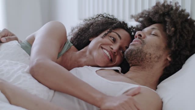 vídeos de stock, filmes e b-roll de happy and cool mature mid adult dark-skinned love couple of mixed race peacefully sleeping and awakening on a new bright day together in a white hotel bed on a early morning. - acariciando
