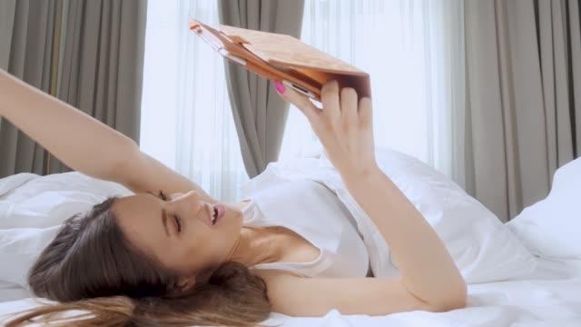 vídeos de stock e filmes b-roll de happy and excited girl in bad celebrating success. using digital tablet. - prémio