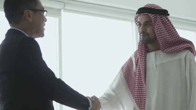 happy arabian man shaking hands with his business partner - saudi arabia stock videos & royalty-free footage