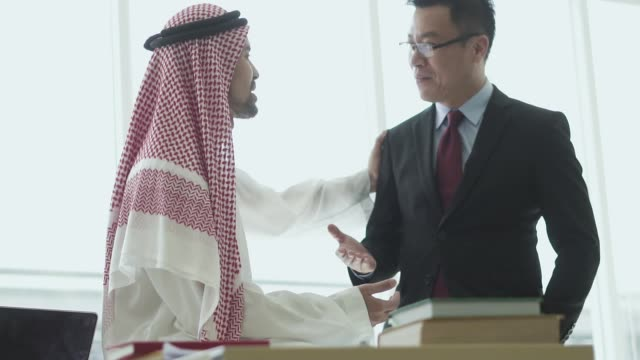 happy arabic and asian businessmen talking friendly to each other - middle eastern culture stock videos & royalty-free footage