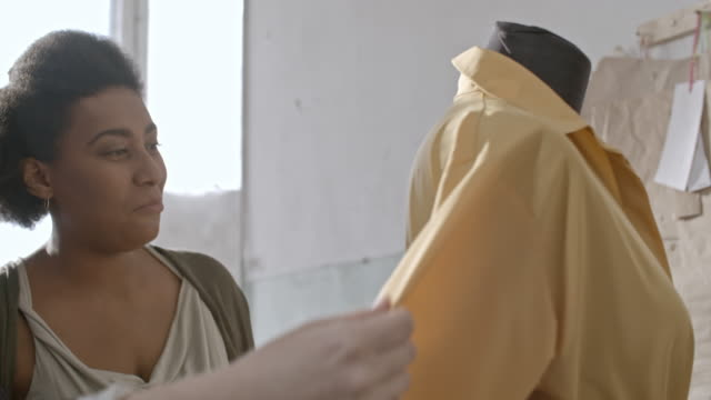 happy asian and african seamstresses looking at dress they made - パタンナー点の映像素材/bロール
