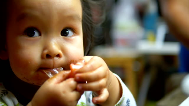 Happy Asian baby girl eating food at home.