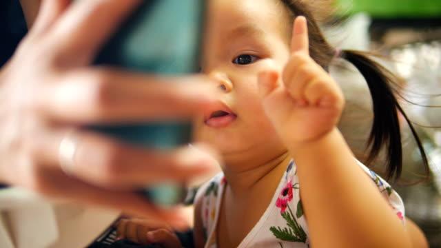 幸せなアジアの赤ちゃん女の子のタッチ スクリーンのスマート フォン。 - 民族衣装点の映像素材/bロール