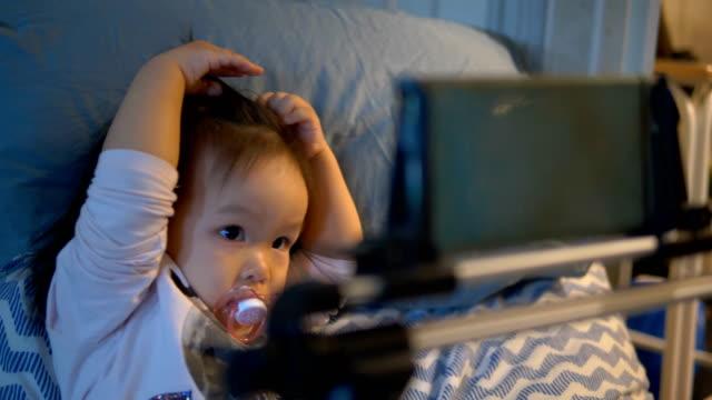 vidéos et rushes de fille heureux bébé asiatique à l'aide de tablette numérique. - doigt humain
