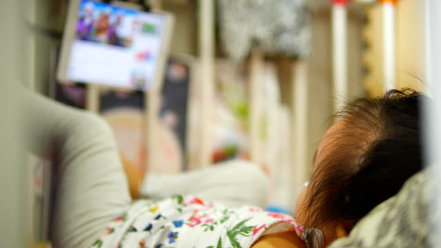 happy asian baby girl watching tablet on the bed. - baby girls stock videos & royalty-free footage