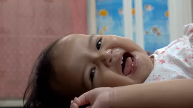 vídeos de stock, filmes e b-roll de um bebê asiático feliz que coloca na cama - só bebês