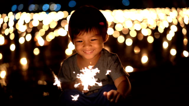slo mo happy asian boy first holding sparklers in hand - igniting stock videos & royalty-free footage