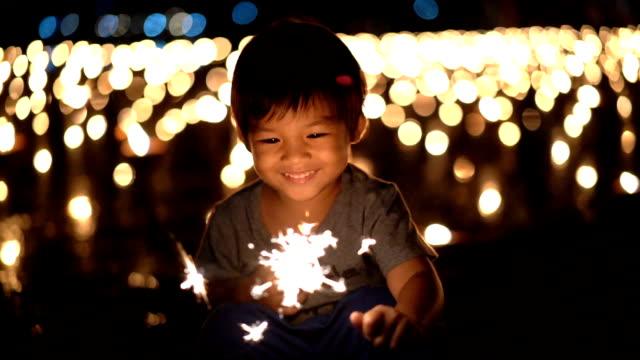 vídeos y material grabado en eventos de stock de slo mo feliz asiatico primera celebración luces de bengala en la mano - vela equipo de iluminación