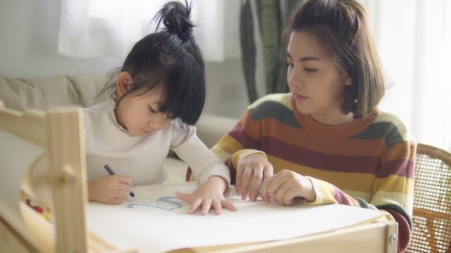 vídeos y material grabado en eventos de stock de niño asiático feliz pintando con crayón con su madre en la sala de estar en casa. - asia sudoriental