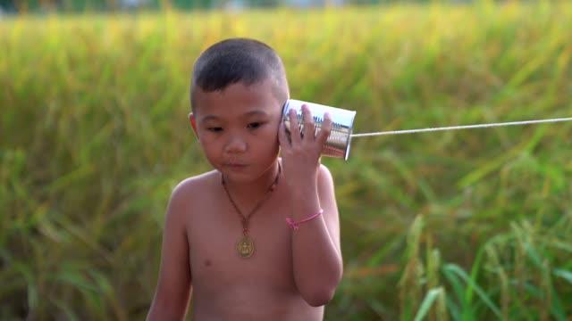 vídeos de stock, filmes e b-roll de jogo asiático feliz do menino no telefone da lata de estanho. - corda
