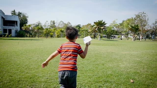 vídeos y material grabado en eventos de stock de asiatico feliz jugando con avión de papel en el parque verde - avión de papel