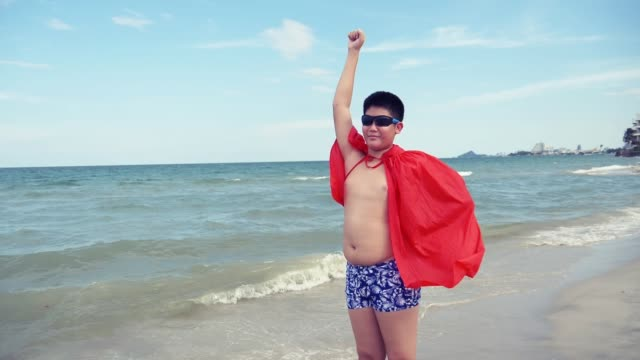 happy asian boy with a red cloth shawl standing on the beach, slow motion. - shawl stock videos & royalty-free footage