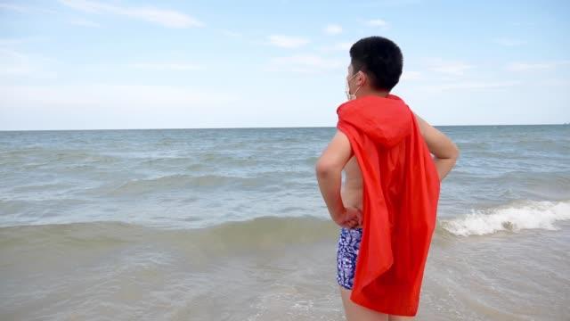 ビーチに立っている赤い布ショールを持つ幸せなアジアの少年、スローモーション。 - 臍点の映像素材/bロール