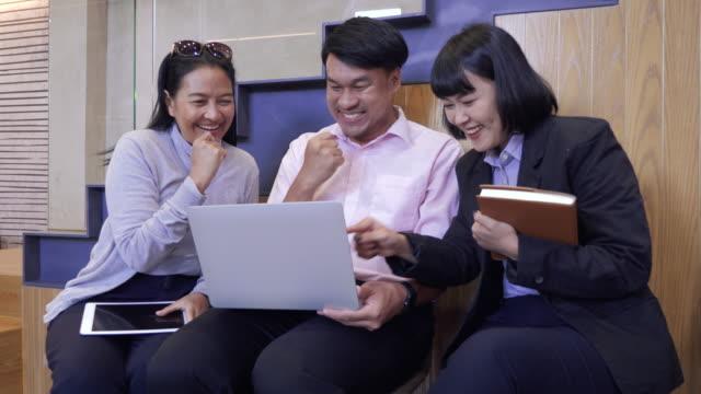 vidéos et rushes de les gens d'affaires asiatiques heureux applaudissent et bras vers le haut célébrant avec le nouveau projet ensemble dans le bureau moderne, l'équipe d'affaires d'entreprise travaillant et le concept réussi - membres du corps humain