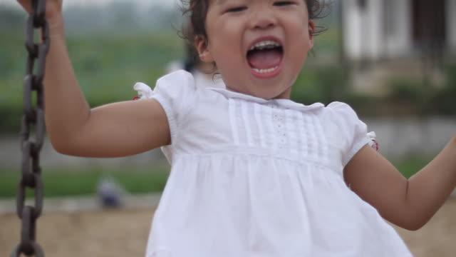 vidéos et rushes de heureux enfant asiatique en profitant du swing avec sa mère, whisky, bouclables - en dernier