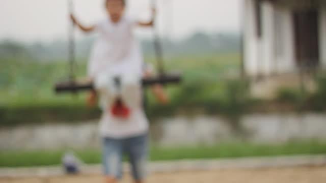 vidéos et rushes de heureux enfant asiatique swing avec sa mère, whisky, bouclables - en dernier
