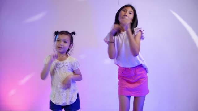 vidéos et rushes de heureux enfants asiatiques dansant ensemble dans house party avec la lumière del à la maison, concept de style de vie. - k pop