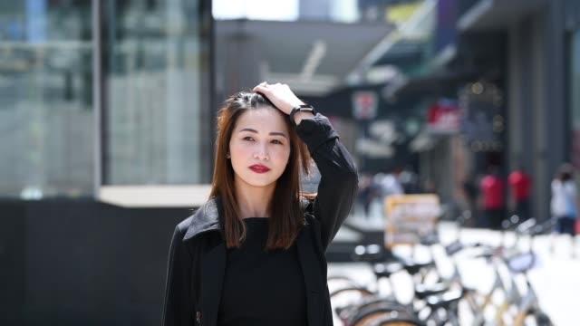 スローモーションで忙しい街を歩いて電話を使用して幸せなアジア中国女性実業家 - 中国人点の映像素材/bロール