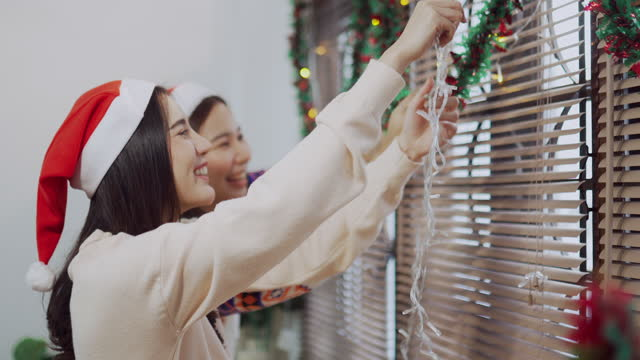 happy asian couple decorate house together in living room for christmas party - chinese ethnicity stock videos & royalty-free footage