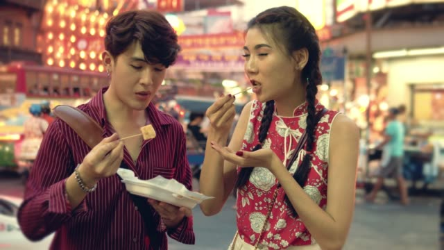 vídeos de stock e filmes b-roll de happy asian couple eating street food in chinese new year festival at bangkok. - cultura chinesa