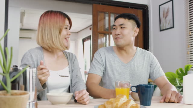 happy asian couple in pajamas sitting at table in kitchen at home in morning and having cereal breakfast together.