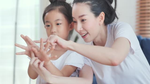happy asian daughter age 6-7 years kids counting with fingers learning to math with mother.young parent mother teaching school child girl helps with homework studying sitting at home table. children education concept,homeschooling and distance learning - schoolgirl stock videos & royalty-free footage