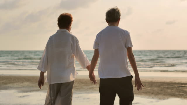 happy asian elderly couple a helping hand and walking to sunset sea surf on sand beach. - married stock videos & royalty-free footage