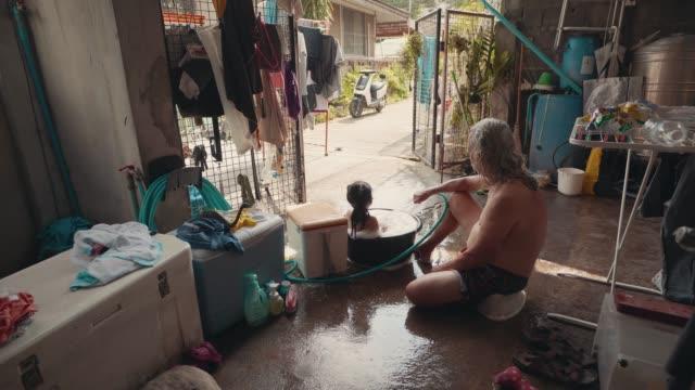 幸せなアジアのファミリーのおじいちゃんと孫は孫たちと一緒にシャワーを浴びて、自宅でキックスイム盆地を学びます。 - 甥点の映像素材/bロール