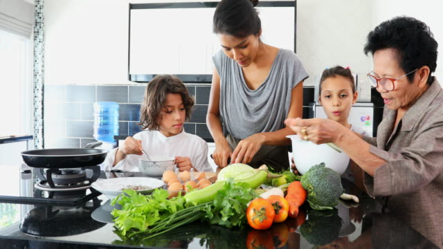 happy asian family cooking together in the kitchen - chores stock videos & royalty-free footage