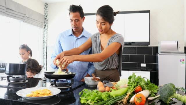 Happy Asian Family Cooking Together in the Kitchen