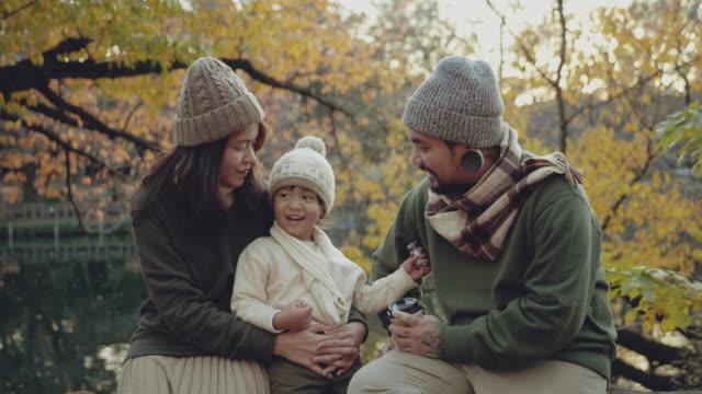 vídeos de stock, filmes e b-roll de família asiática feliz curtindo juntos na temporada de outono na floresta. - família de duas gerações