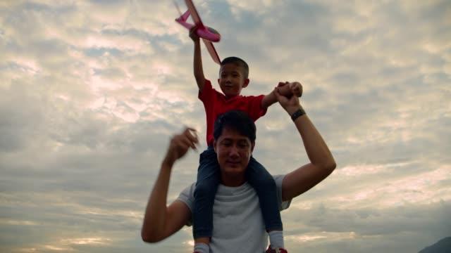 vídeos y material grabado en eventos de stock de feliz padre de la familia asiática madre e hija jugando en el parque natural al atardecer.4k dci imágenes a cámara lenta. - picnic