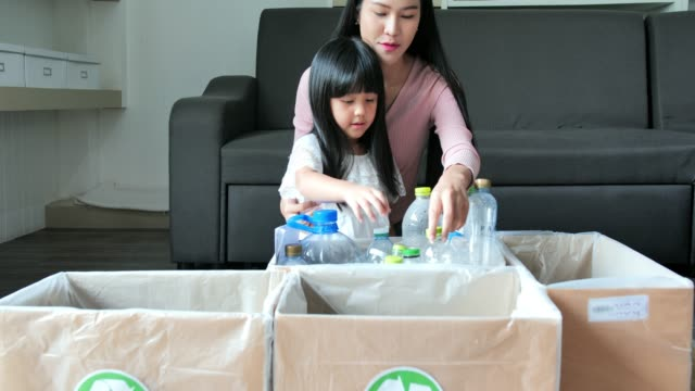 happy asian family of mother teaching smiling daughter how to recycle household waste.charity, people and ecology concept.recycling and ecology.lifestyle - ecological education and awareness concept.recycling in daily life - recycling stock videos & royalty-free footage