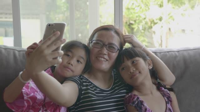リビングルームにスマートフォンで自分撮りを取って幸せなアジアの家族。 - 自画像点の映像素材/bロール