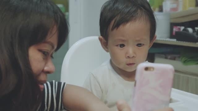 vídeos de stock, filmes e b-roll de felizes asiáticas família videoconferências no smartphone. - voz