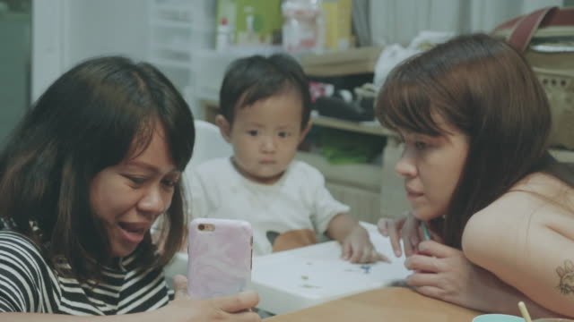 happy asian family video conferences on smartphone. - baby waving stock videos & royalty-free footage