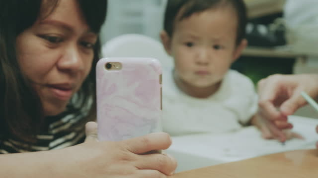 happy asian family video conferences on smartphone. - 6 11 months stock videos & royalty-free footage