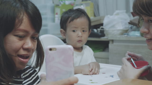 vídeos y material grabado en eventos de stock de felizes asia familiares video conferencias en smartphone. - 6 11 months