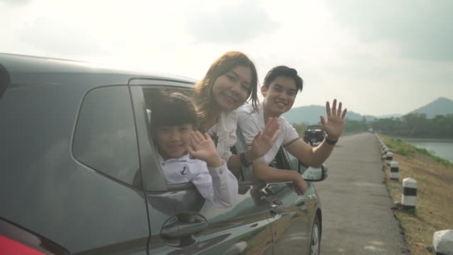 happy asian family with father, mother and daughter in compact car are smiling and bye bye when driving for travel on vacation. car insurance or rental and family happy to journey concept. - divisione video stock e b–roll